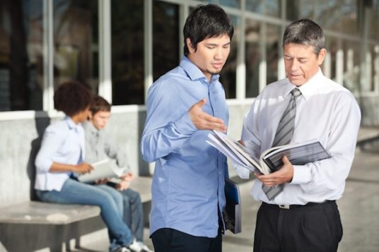 teacher discussing with student on college campus